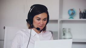 Call center operator talking with a customer and smiling stock footage