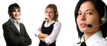 Call center operator team. Two attractive young customer service representative ladies and a young call center operator guy are smiling and they are talking to Royalty Free Stock Photo