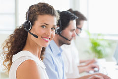Call center operator wearing headset in office. Portrait of young call center operator wearing headset with colleagues working in background at office Stock Photos