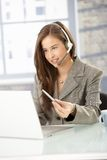 Call center operator at work. Smiling call center operator girl at work, looking at screen, speaking to headset stock photo