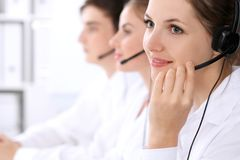 Call center operators. Focus at beautiful woman in headset royalty free stock photography