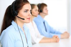 Call center operators. Focus at  business woman in headset. Call center operators. Focus at brunette business women in headset Royalty Free Stock Images