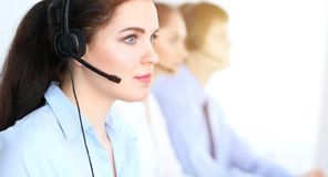 Call center operators at work. Focus at business woman in headset stock photos