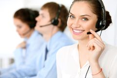 Call center operators. Focus at  business woman in headset. Call center operators. Focus at brunette business women in headset Royalty Free Stock Photo