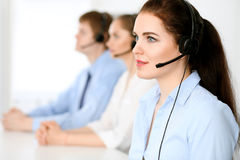 Call center operators. Focus at  business woman in headset. Call center operators. Focus at brunette business women in headset Stock Photos