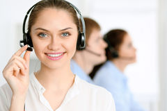 Call center operators. Focus at  business woman in headset. Call center operators. Focus at brunette business women in headset Royalty Free Stock Photography