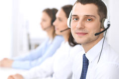 Call center operators. Focus at businessman in headset while consulting customers Stock Images