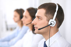 Call center operators. Focus at businessman in headset while consulting customers.  Royalty Free Stock Photography