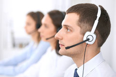 Call center operators. Focus at businessman in headset while consulting customers.  Royalty Free Stock Photo
