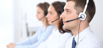 Call center operators. Focus at businessman in headset while consulting customers Stock Photos