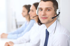 Call center operators. Focus at businessman in headset while consulting customers Stock Photo
