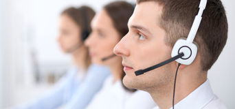 Call center operators. Focus at businessman in headset while consulting customers Royalty Free Stock Image