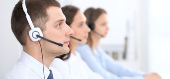Call center operators. Focus at businessman in headset while consulting customers Stock Image