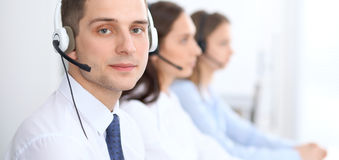 Call center operators. Focus at businessman in headset while consulting customers Royalty Free Stock Photos
