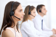 Call center operators. Focus at young beautiful business woman in headset. Call center operators. Focus at young beautiful business women in headset Royalty Free Stock Photography