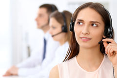 Call center operators. Focus at young beautiful business woman in headset. Call center operators. Focus at young beautiful business women in headset Royalty Free Stock Photo