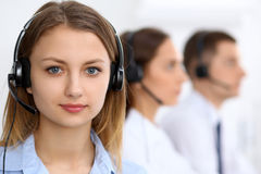 Call center operators. Focus at young beautiful business woman in headset Stock Photos
