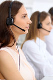 Call center operators. Focus at young beautiful business woman in headset. Call center operators. Focus at young beautiful business women in headset Royalty Free Stock Images