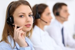 Call center operators. Focus at young beautiful business woman in headset Royalty Free Stock Photos