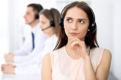 Call center operators. Focus on young cheerful smiling woman in headset. Business and customer service concepts stock images