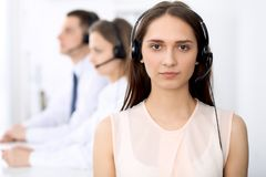 Call center operators. Focus on young cheerful smiling woman in headset. Business and customer service concepts stock photos