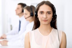 Call center operators. Focus on young cheerful smiling woman in headset. Business and customer service concepts royalty free stock images