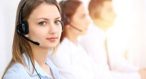 Call center operators. Focus on young cheerful smiling woman in headset. Business and customer service concepts stock photography