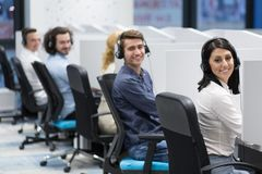 Call center operators. Group of young business people with headset working and giving support to customers in a call center office Stock Images