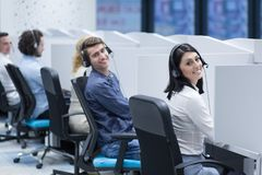 Call center operators. Group of young business people with headset working and giving support to customers in a call center office Royalty Free Stock Photos