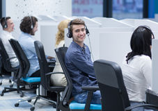 Call center operators. Group of young business people with headset working and giving support to customers in a call center office Stock Photos