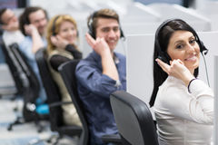 Call center operators. Group of young business people with headset working and giving support to customers in a call center office Stock Image