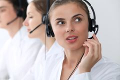 Call center operators at work. Focus at beautiful business woman in headset stock photography