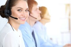 Call center operators at work. Focus at business woman in headset royalty free stock photo