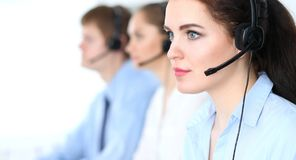 Call center operators at work. Focus at business woman in headset stock photography