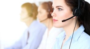 Call center operators at work. Focus at business woman in headset royalty free stock image