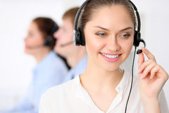 Call center operators. Young beautiful business woman in headset. Male call operator in headset at the background Stock Image