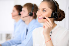 Call center operators. Young beautiful business woman in headset. Male call operator in headset at the background Royalty Free Stock Photography