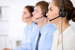 Call center operators. Young beautiful business woman in headset. Male call operator in headset at the background. Call center operators. Young beautiful Royalty Free Stock Photo