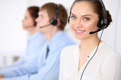 Call center operators. Young beautiful business woman in headset. Male call operator in headset at the background Stock Photography