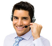 Call Center Representative Talking On Headset. Portrait of smiling male call center representative talking on headset over white background. Horizontal shot Stock Photo