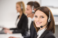 Call center. Smiling beautiful lady working at call center with colleagues in office Stock Images