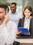 Call center. Smiling beautiful lady working at call center with colleagues in office Stock Photos