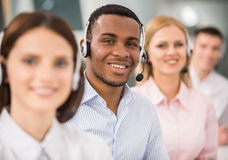 Call center. Smiling call center employees sitting in line with their headsets Stock Photos