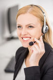 Call center. Smiling young woman in suit sitting at call center office and working Royalty Free Stock Photography