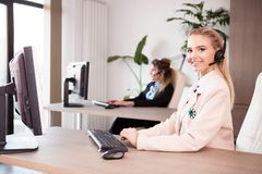 Call center telemarketing support center with working women. At their desk Stock Image