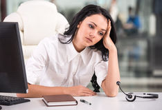 Call center. Tired young woman is sitting at the table at work in a call center Royalty Free Stock Images