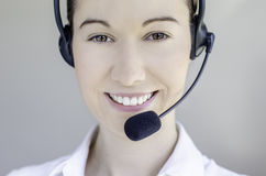 Call center woman. Brunette girl with headphones communicate with customers Stock Image