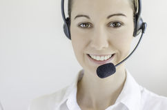 Call center woman. Brunette girl with headphones communicate with customers Royalty Free Stock Photo