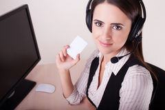 Call center woman with headset showing business card. Stock Photo