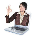 Call center woman with headset smiling out of the laptop Royalty Free Stock Photo